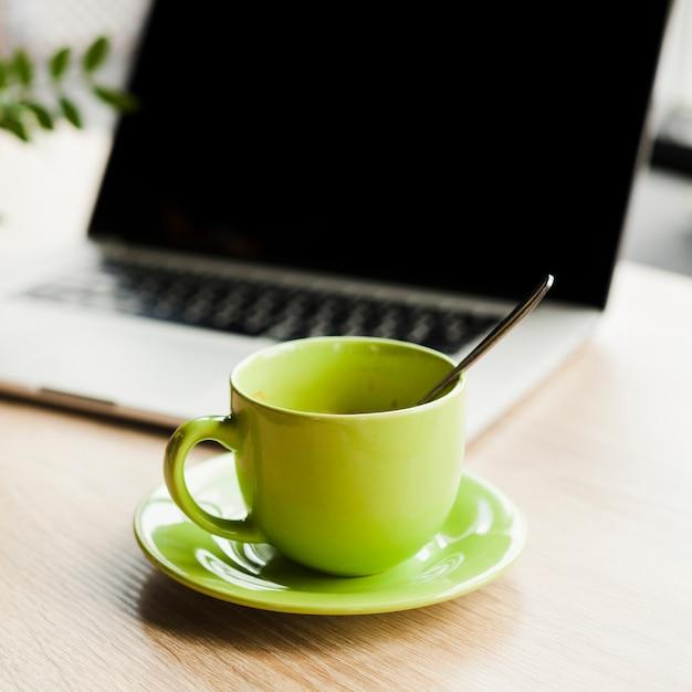 Xícara de café verde e laptop aberto na mesa de madeira Foto gratuita