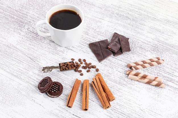 Xícara de café vista superior com biscoitos e canela na mesa branca Foto gratuita