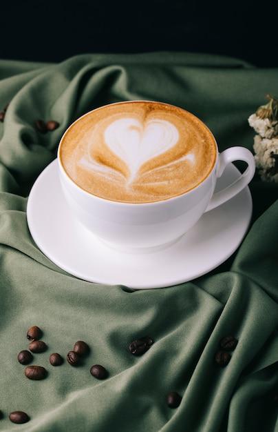 Xícara de cappuccino com grãos de café na mesa Foto gratuita