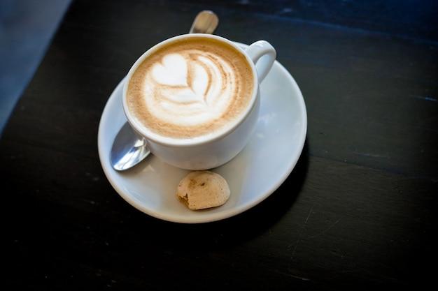 Xícara de cappuchino ou café com leite em um copo branco com espuma em forma de coração e cookies Foto Premium