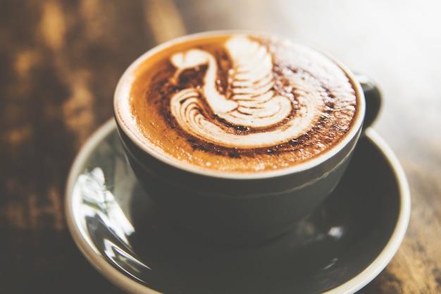 Xícara de cappucino quente está sobre a mesa de madeira Foto Premium