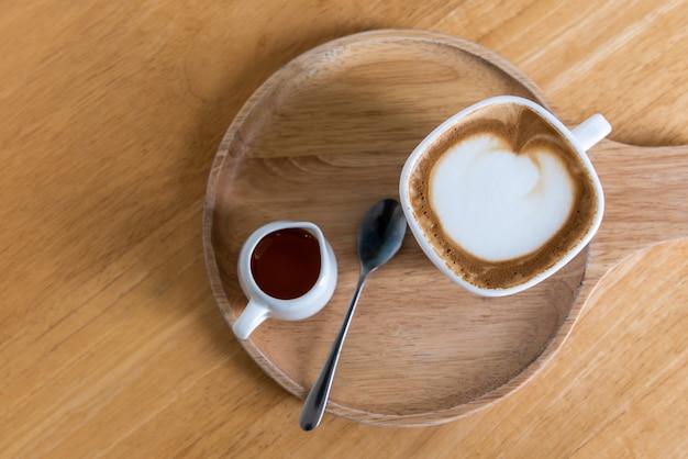 Xícara de capuccino café com açúcar e colher na placa de madeira e mesa de madeira, vista superior Foto Premium
