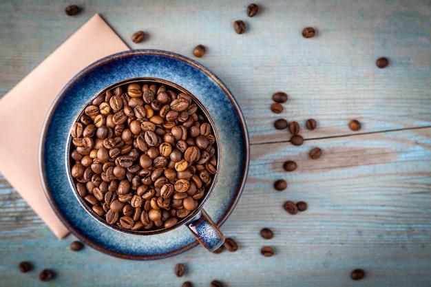Xícara de capuccino plana leigos com grãos de café espalhados na mesa, closeup de vista superior de xícara de café azul sobre fundo de madeira na luz do sol Foto Premium