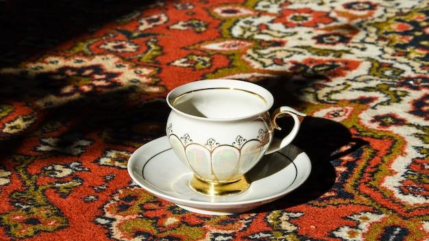 Xícara de chá à moda antiga no tapete turco ornamentado, café turco autêntico e um café em um restaurante turco, intervalo para o chá Foto Premium