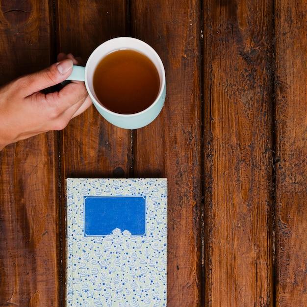 Xícara de chá aromático e livro na madeira velha Foto gratuita