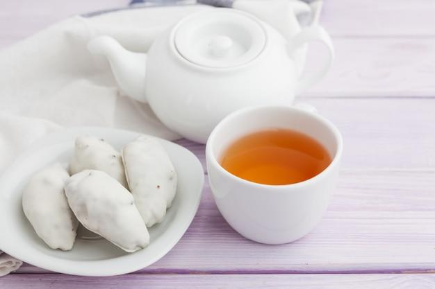 Xícara de chá com biscoitos sobre fundo de madeira lilás Foto Premium