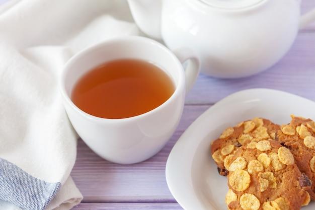 Xícara de chá com biscoitos sobre madeira lilás Foto Premium