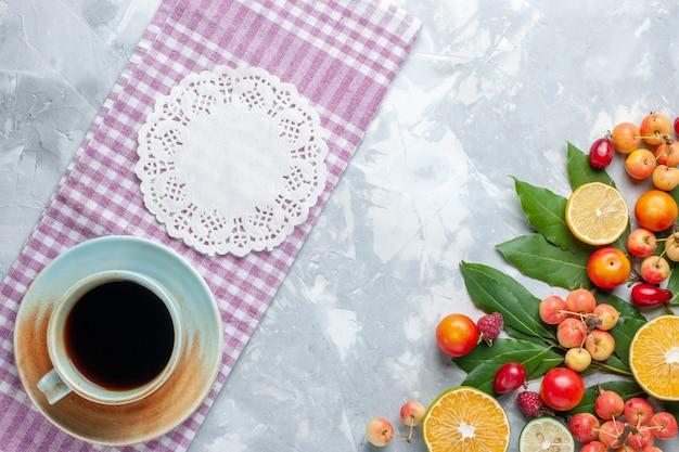 Xícara de chá com cerejas e outras frutas na mesa clara com vista de cima Foto gratuita