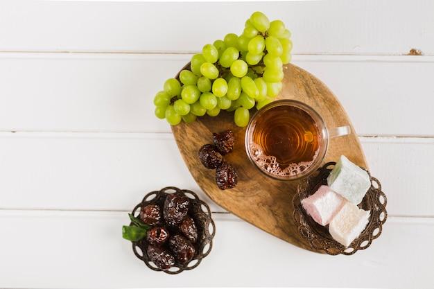 Xícara de chá com doces e uvas orientais Foto gratuita