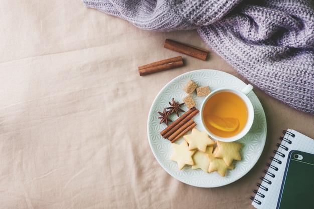 Xícara de chá com limão e biscoitos, mel e paus de canela, anis estrelado no cobertor Foto Premium