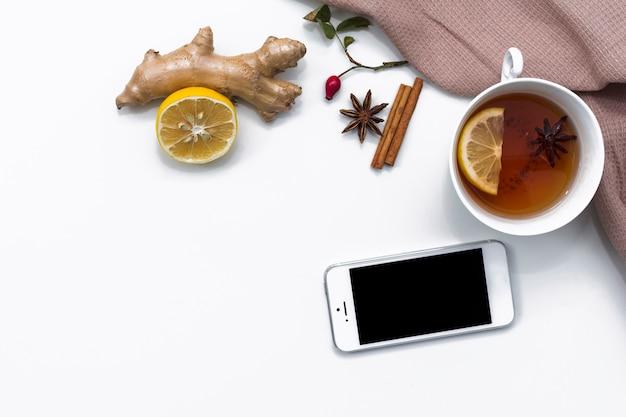 Xícara de chá com limão e gengibre perto de smartphone Foto gratuita