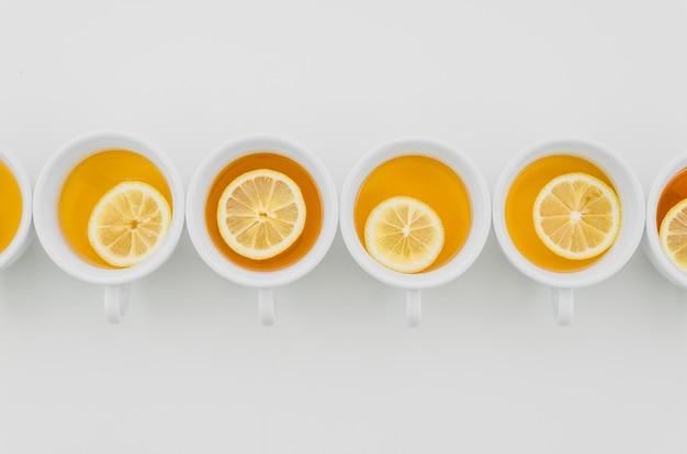 Xícara de chá com limões isolado no fundo branco Foto gratuita