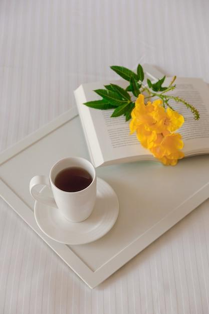 Xícara de chá com um livro em uma bandeja branca com uma flor amarela em uma cama branca Foto Premium