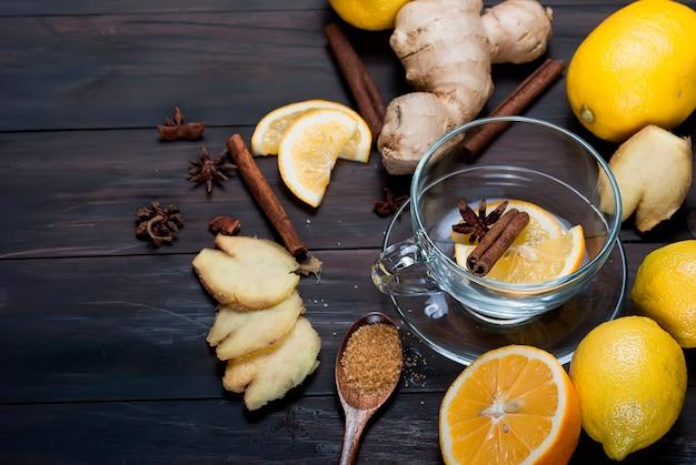 Xícara de chá de gengibre com limão e mel em madeira marrom escuro Foto Premium