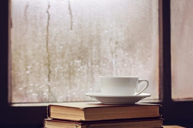 Xícara de chá de outono ou coffeeon janela chuvosa Foto Premium