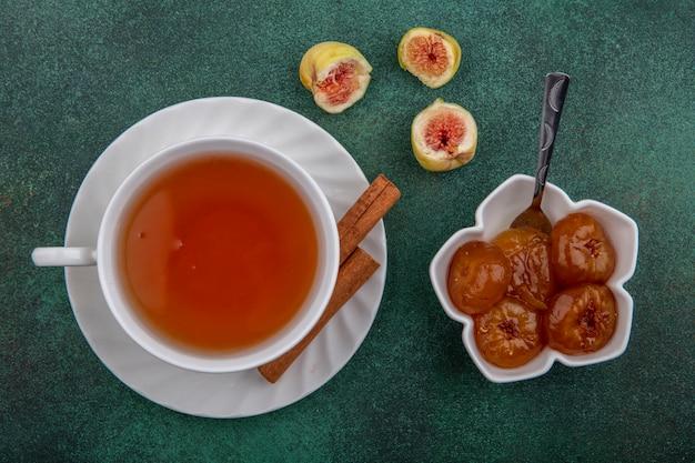 Xícara de chá de vista superior com canela e geléia de figo no fundo verde Foto gratuita