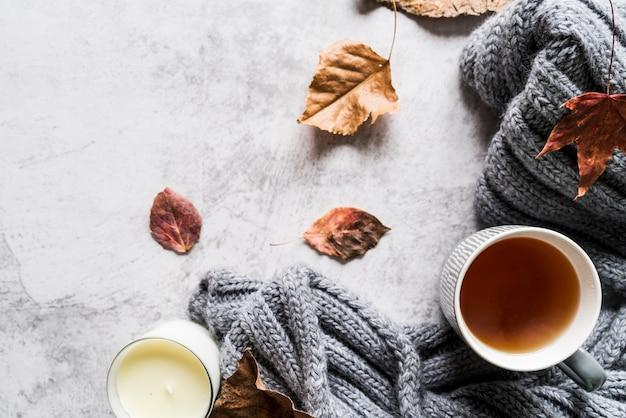 Xícara de chá e cachecol entre folhas Foto gratuita