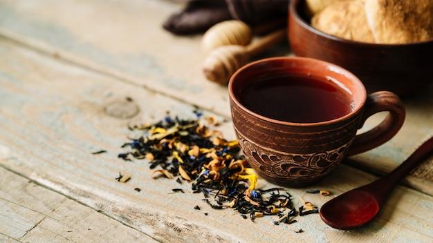 Xícara de chá e ervas no fundo de madeira Foto gratuita