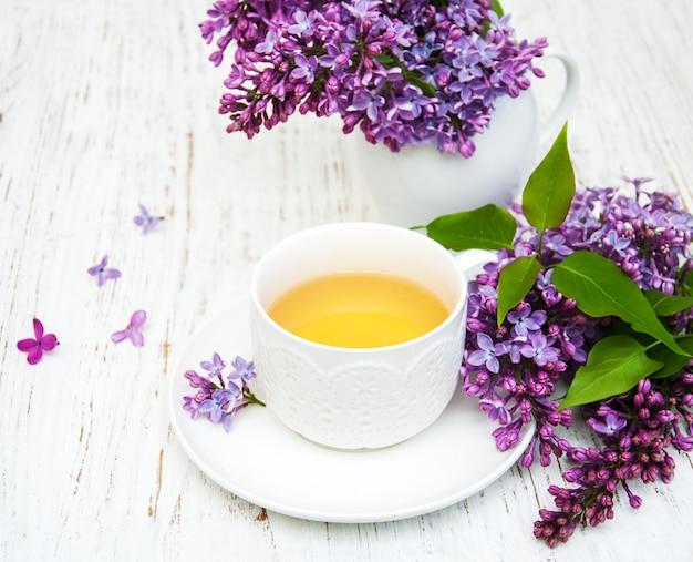 Xícara de chá e flores lilás Foto Premium
