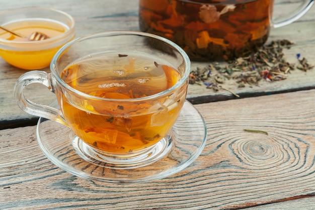 Xícara de chá e folhas de chá na mesa de madeira Foto Premium