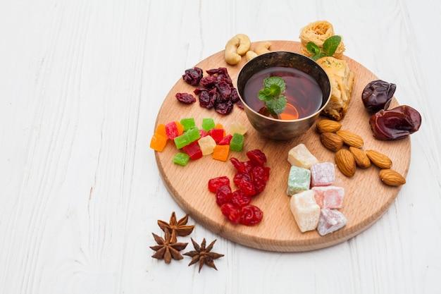 Xícara de chá e sobremesas turcas frescas na bandeja Foto gratuita