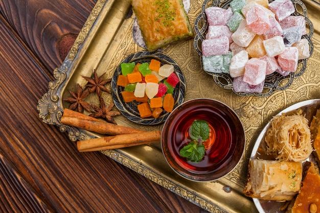 Xícara de chá e sobremesas turcas na bandeja Foto gratuita