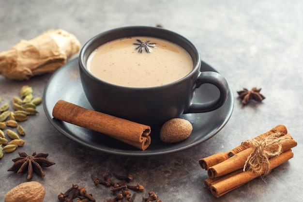 Xícara de chá indiano tradicional masala chai com ingredientes. canela, cardamomo, anis, noz-moscada. Foto Premium