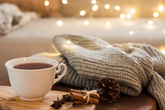 Xícara de chá na almofada de madeira com manta de malha Foto gratuita