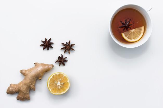 Xícara de chá perto de metade de gengibre e limão Foto gratuita