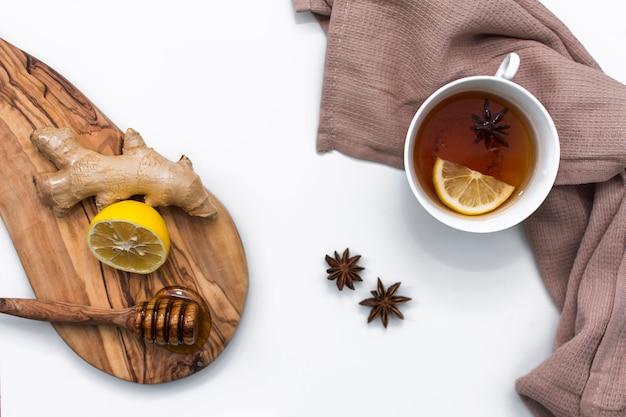 Xícara de chá perto de placa de madeira com mel e limão Foto gratuita