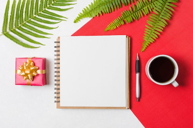 Xícara de chá preto; caneta; bloco de notas e caixa de presente, dispostas em uma linha sobre a superfície vermelha e branca Foto gratuita