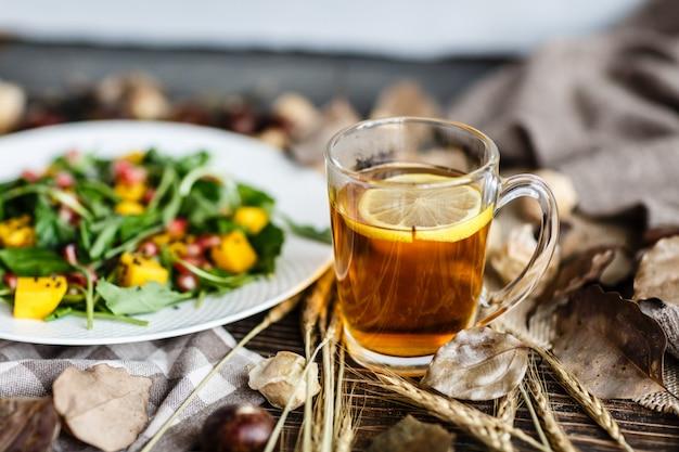 Xícara de chá preto com limão e salada com manga, sementes de romã na chapa branca Foto Premium