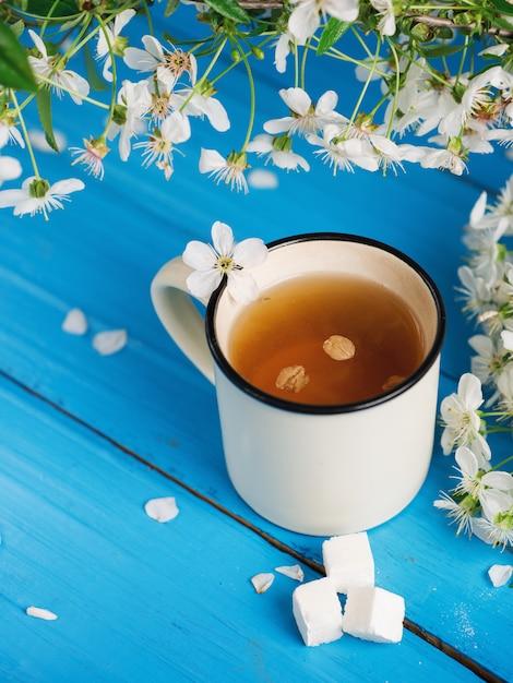 Xícara de chá primavera, flor de cerejeira sobre fundo azul de madeira Foto Premium
