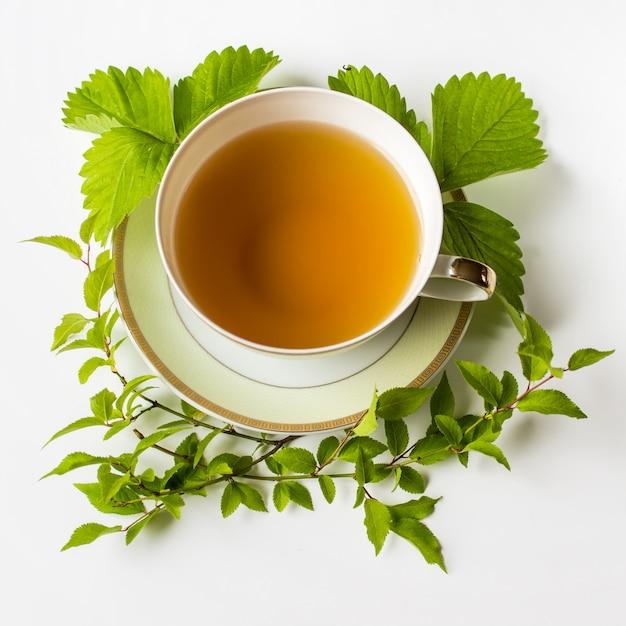 Xícara de chá verde decorado em círculo com folhas de morango e galhos com folhas verdes Foto Premium