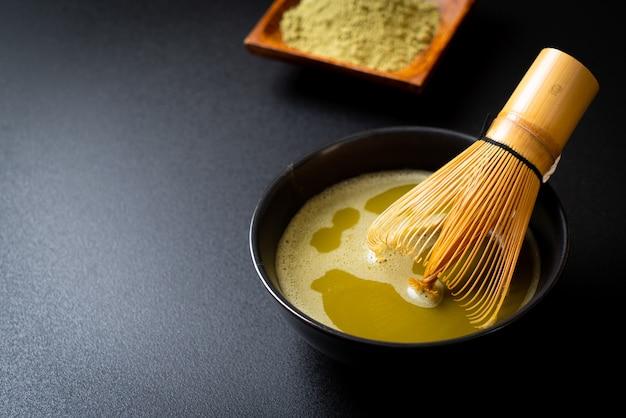 Xícara de chá verde matcha quente com pó de chá verde e batedor de bambu Foto Premium
