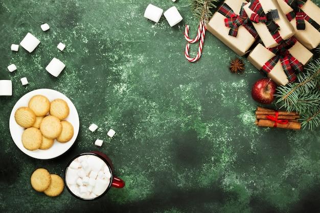 Xícara de chocolate quente, biscoitos e vários atributos de férias em uma superfície verde Foto Premium