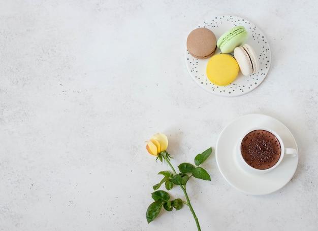 Xícara de chocolate quente com flores macarons Foto Premium