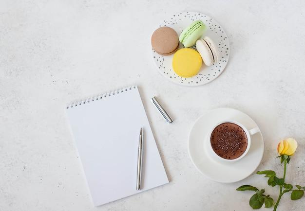 Xícara de chocolate quente com macarons, flor e bloco de notas Foto Premium