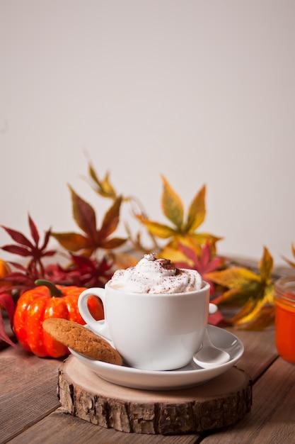 Xícara de chocolate quente e cremoso com espuma com folhas de outono e abóboras Foto Premium