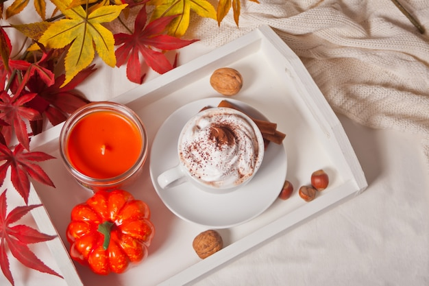 Xícara de chocolate quente e cremoso com espuma na bandeja branca com folhas de outono e abóboras no fundo Foto Premium