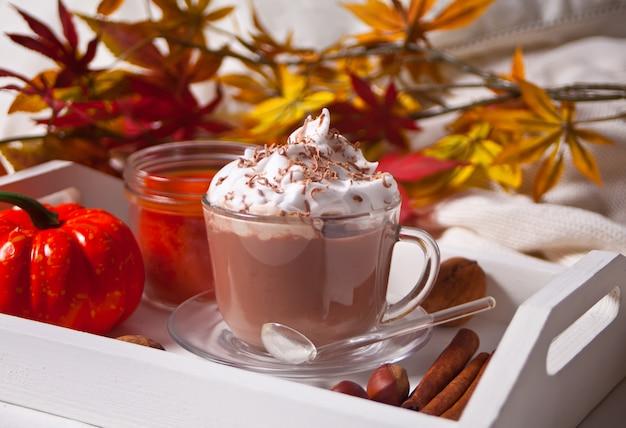 Xícara de chocolate quente e cremoso com espuma na bandeja branca com folhas de outono e abóboras Foto Premium