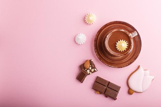 Xícara de chocolate quente e pedaços de chocolate ao leite com amêndoas em fundo rosa. vista do topo. Foto Premium