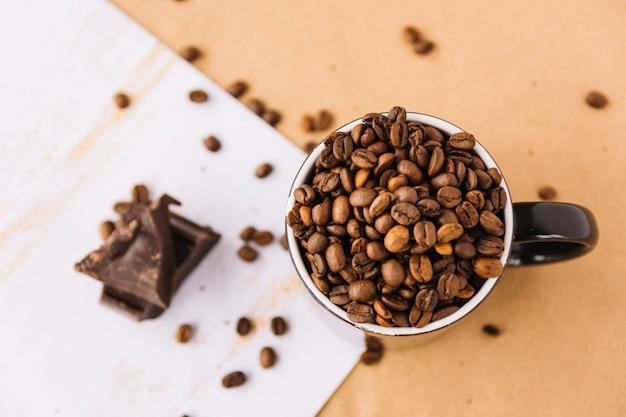 Xícara de grãos de café na folha Foto gratuita
