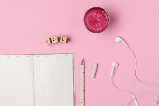Xícara de latte de beterraba rosa superalimento na moda, caneta, bloco de notas Foto Premium