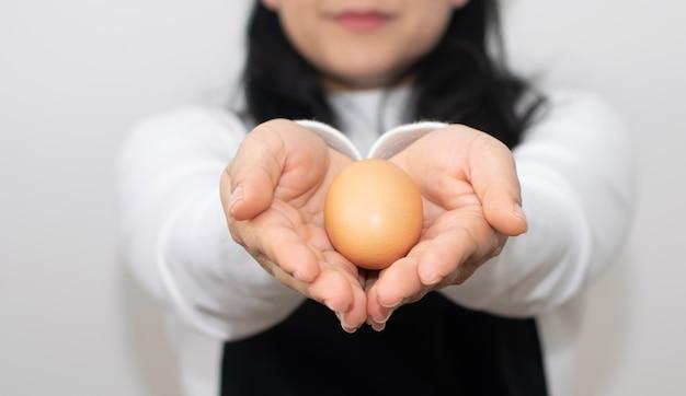 Xícara de mulher, duas mãos juntas para segurar ovo fresco Foto Premium