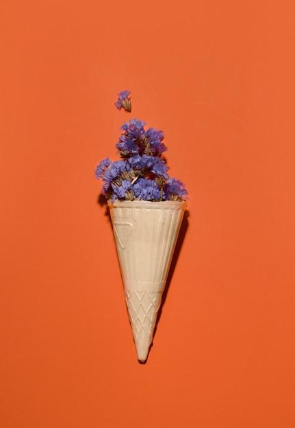 Xícara de waffle com flores roxas em um espaço laranja. copie o espaço. Foto Premium