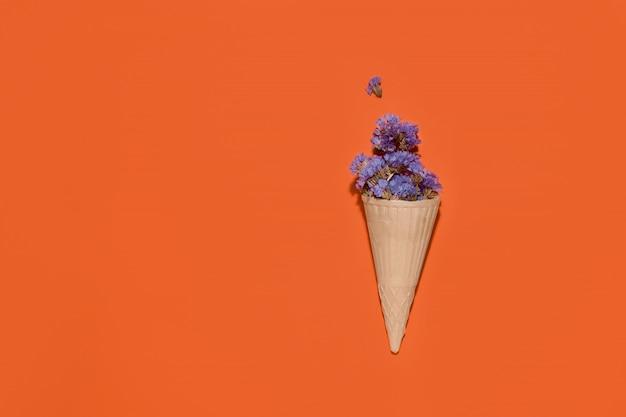 Xícara de waffle para sorvete com flores azuis em um espaço laranja. copie o espaço Foto Premium