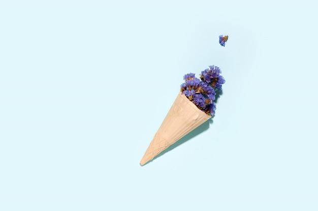 Xícara de waffle para sorvete com flores em um espaço azul. copie o espaço. conceito de verão Foto Premium