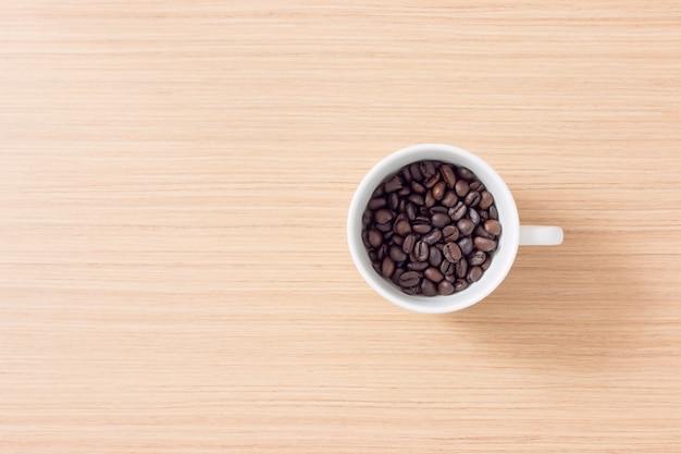 Xícara e grãos de café sobre fundo de madeira com espaço de cópia Foto Premium