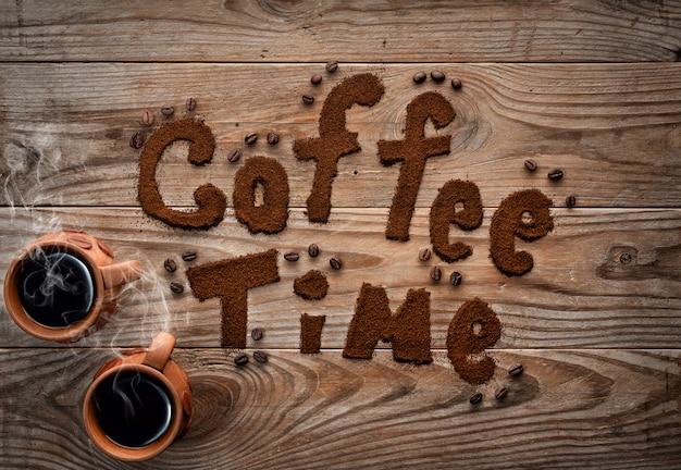 Xícaras de café com vapor no plano de fundo texturizado de madeira. Foto Premium